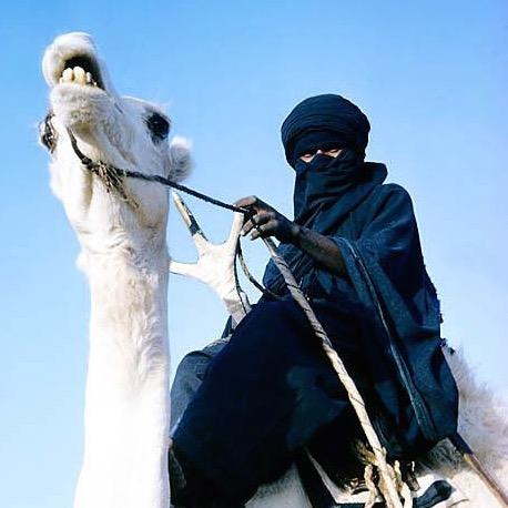 Nomade trotseert de hitte van de woestijn.